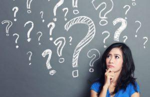 בחורה חושבת ליד לוח עם סימני שאלה